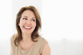 Cheerful mature woman looking away isolated over white background