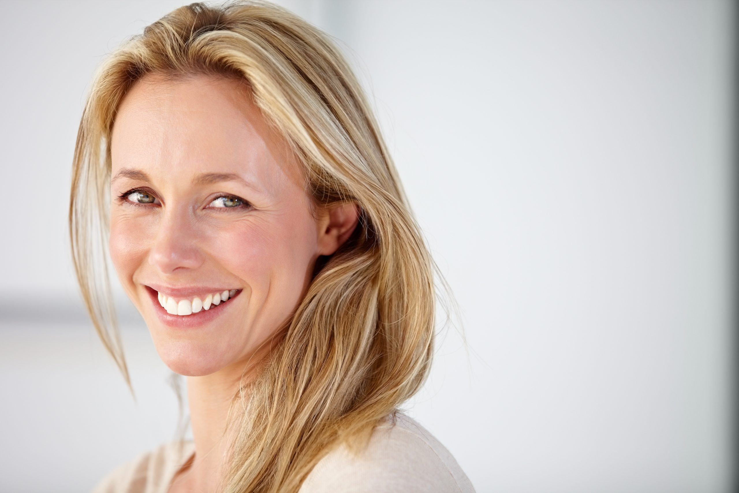 portrait of a blonde haired woman smiling against a white background