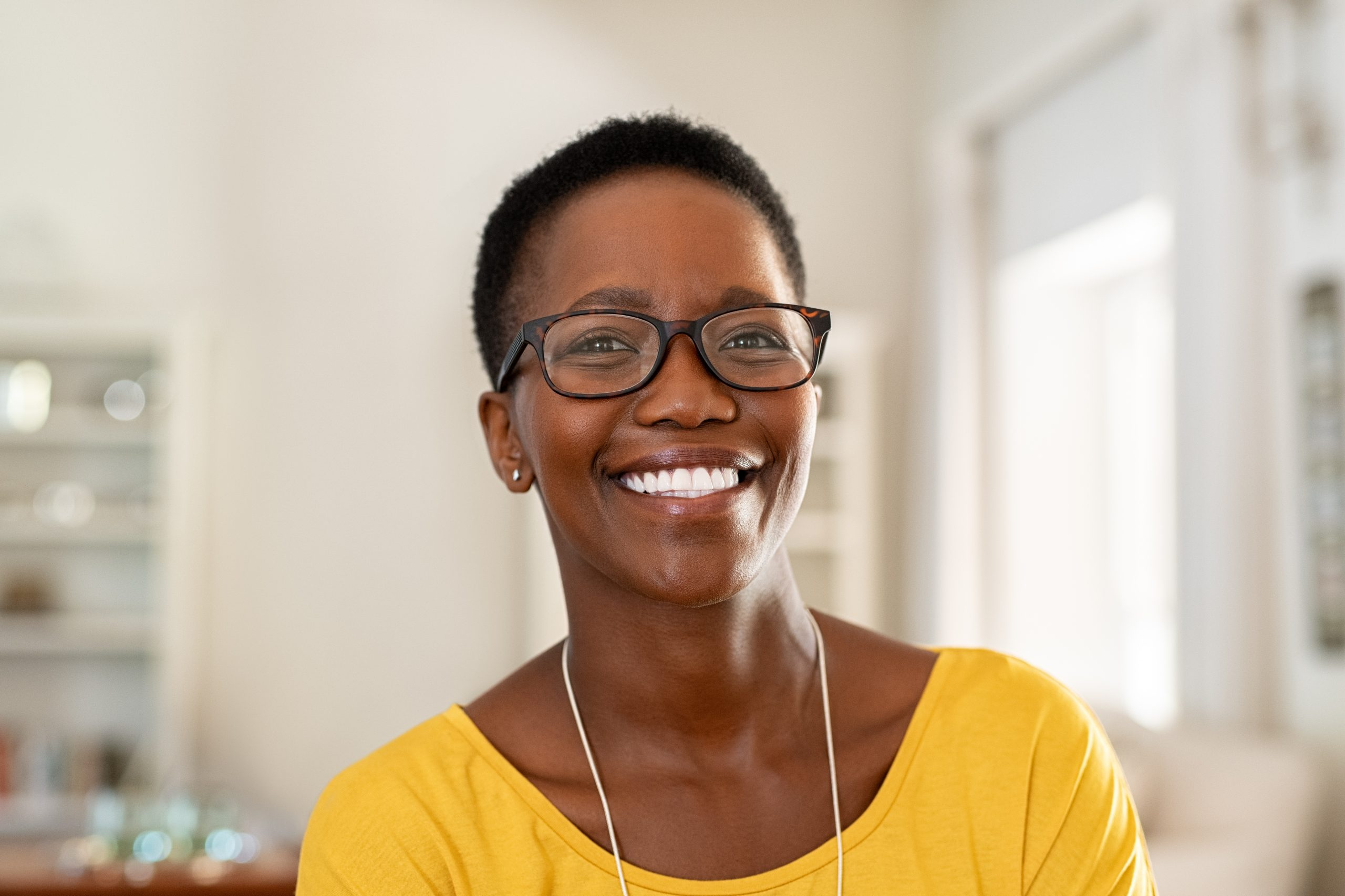 Cheerful african american lady with glasses and short hair.
