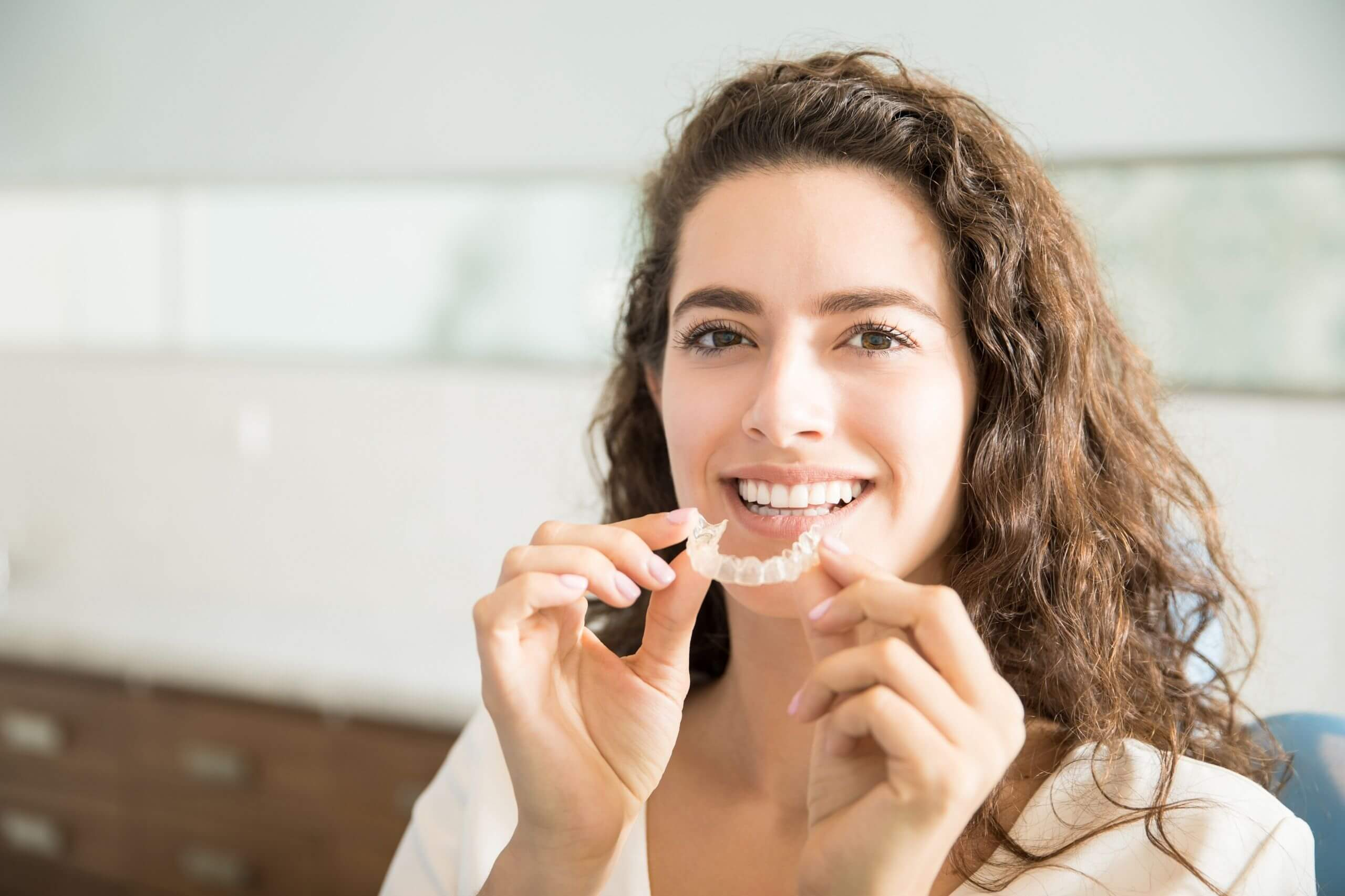 A woman holding invisalign braces and smiling, Harwood Dental Care