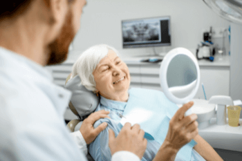 An older woman looking in the mirror at the dentist